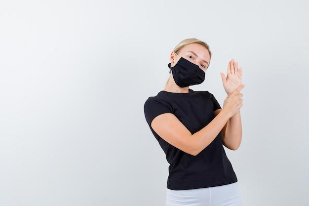 Blonde frau, die hand am handgelenk hält und stoppschild im schwarzen t-shirt zeigt