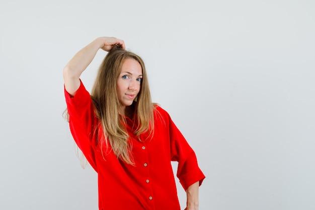 Blonde frau, die hand auf kopf im roten hemd hält und faszinierend schaut.