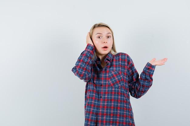 Blonde frau, die hand hebt, während hand auf ohr drückt, kamera im karierten hemd aufwirft und überrascht schaut. vorderansicht.