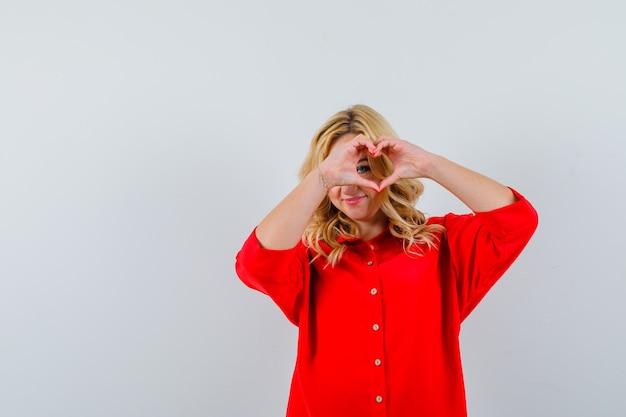 Blonde frau, die herzform mit den fingern in der roten bluse macht und glücklich schaut