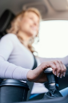 Blonde frau, die ihr auto fährt