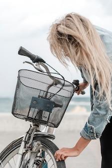 Blonde frau, die ihr fahrrad repariert