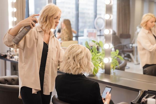 Blonde frau, die ihr haar erledigt bekommt