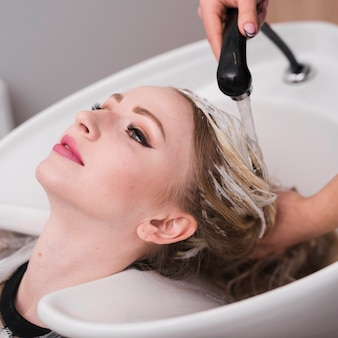 Blonde frau, die ihr haar gewaschen erhält