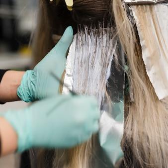 Blonde frau, die ihre haarfärbung erhält