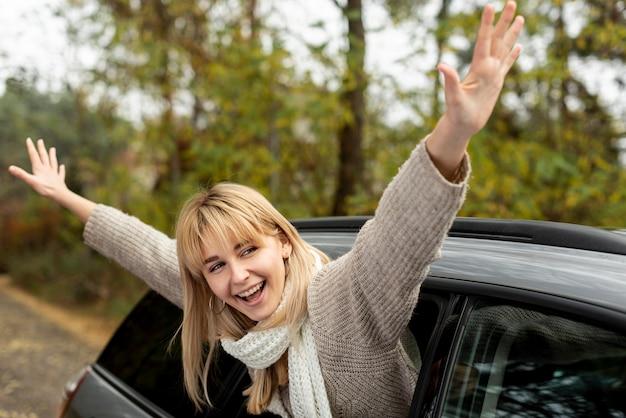 Blonde frau, die ihre hände aus auto heraus nimmt