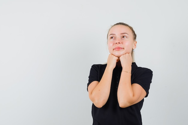 Blonde frau, die ihre hände unter kinn im schwarzen t-shirt setzt