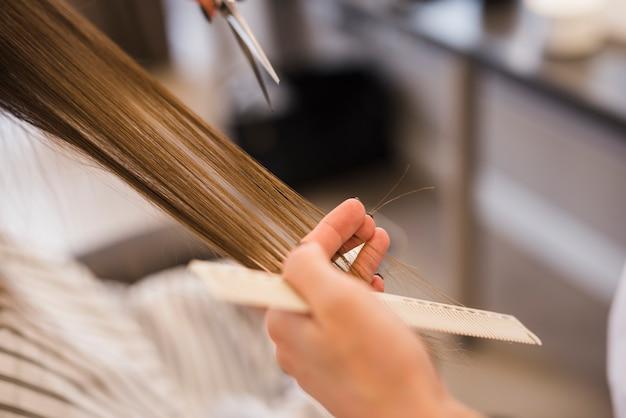 Blonde frau, die ihren haarschnitt erhält