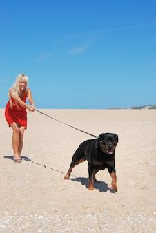Blonde frau, die ihren hund am strand geht