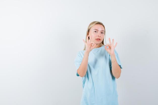 Blonde frau, die in blauem t-shirt gute zeichen zeigt und selbstbewusst aussieht