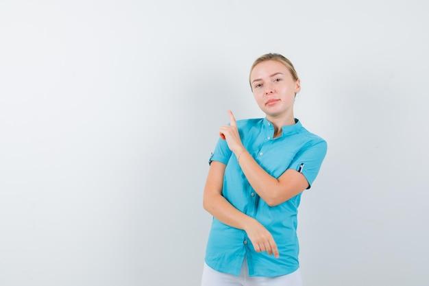 Blonde frau, die in blauer bluse nach oben zeigt und isoliert hoffnungsvoll aussieht