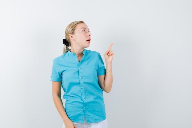 Blonde frau, die in blauer bluse nach oben zeigt und isoliert schaut