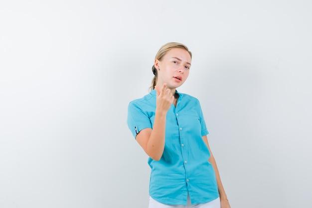 Blonde frau, die in blauer bluse zeigt und zögerlich isoliert aussieht
