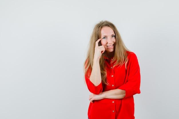 Blonde frau, die in der denkenden haltung im roten hemd steht und glücklich schaut,