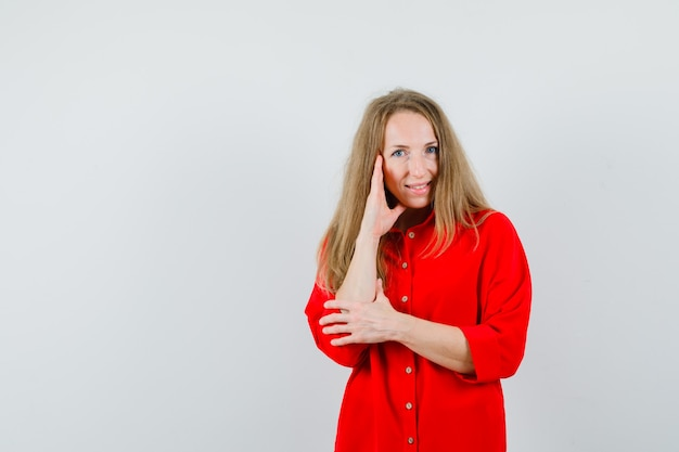 Blonde frau, die in der denkenden pose im roten hemd steht und fröhlich schaut,