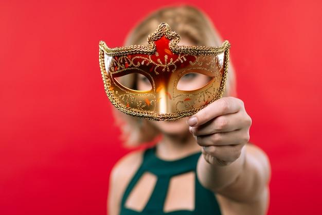 Blonde frau, die in der hand orange maske hält