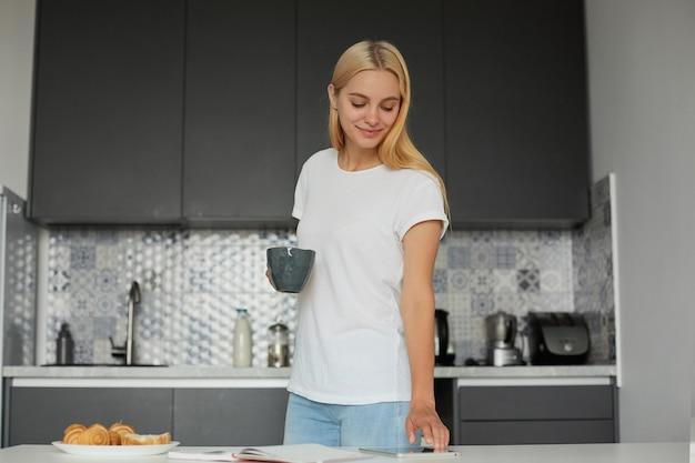 Blonde frau, die in der nähe des tisches steht, lächelt, frühstückt, ihren tag plant, hält eine große graue tasse
