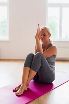 Blonde frau, die in der sportkleidung meditiert