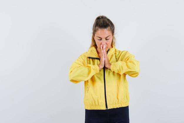 Blonde frau, die in gelber bomberjacke und in schwarzen hosen betet und konzentriert schaut