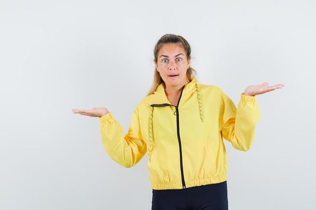 Blonde frau, die in verwirrter geste in der gelben bomberjacke und in der schwarzen hose steht und verblüfft aussieht Kostenlose Fotos