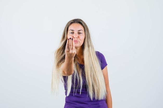 Blonde frau, die italienische geste im violetten t-shirt, vorderansicht tut.