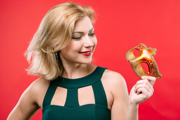 Blonde frau, die karnevalsmaske betrachtet