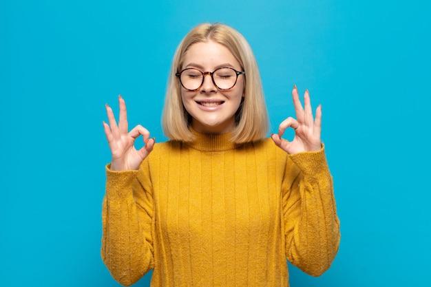 Blonde frau, die konzentriert und meditierend aussieht, sich zufrieden und entspannt fühlt, denkt oder eine wahl trifft