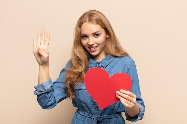 Blonde frau, die lächelt und freundlich aussieht, die nummer vier oder vier mit der hand nach vorne zeigt und herunterzählt