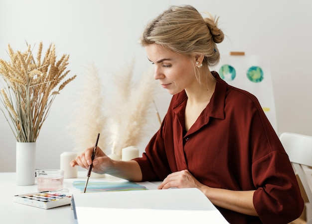 Blonde frau, die mit aquarellen malt