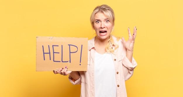 Blonde frau, die mit den händen in der luft schreit und sich wütend, frustriert, gestresst und verärgert fühlt