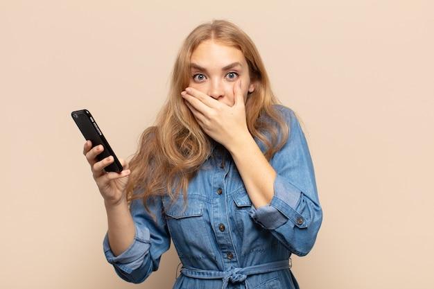 Blonde frau, die mit einem schockierten, überraschten ausdruck den mund mit den händen bedeckt, ein geheimnis hält oder oops sagt