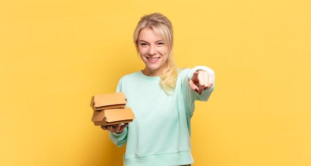 Blonde frau, die mit einem zufriedenen, selbstbewussten, freundlichen lächeln auf die kamera zeigt und sie wählt