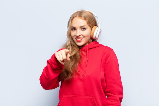 Blonde frau, die mit einem zufriedenen, selbstbewussten, freundlichen lächeln auf kamera zeigt und sie wählt