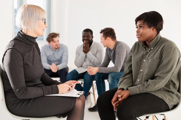 Blonde frau, die mit weiblichem rehabilitationspatienten spricht
