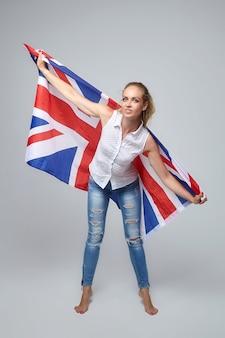 Blonde frau, die mit weiß der britischen flagge aufwirft