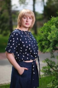 Blonde frau, die nahe grünem busch steht