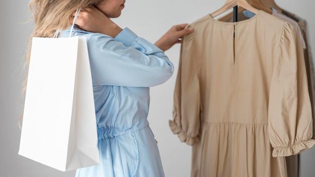 Blonde frau, die neue kleider prüft