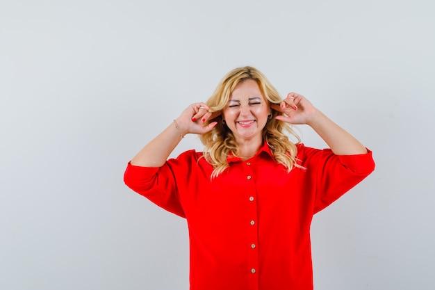 Blonde frau, die ohren mit zeigefingern in roter bluse verstopft und gehetzt aussieht
