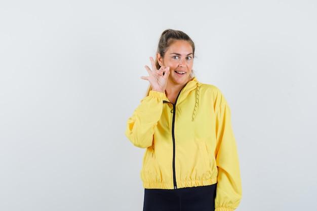 Blonde frau, die ok zeichen in der gelben bomberjacke und in der schwarzen hose zeigt und glücklich schaut