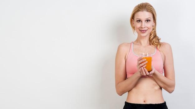 Blonde frau, die orangensaft trinkt