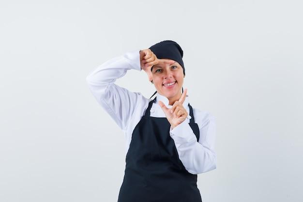 Blonde frau, die rahmengeste mit händen in der schwarzen kochuniform zeigt und hübsch, vorderansicht schaut.