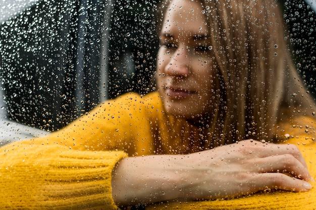 Blonde frau, die regen durch das fenster betrachtet