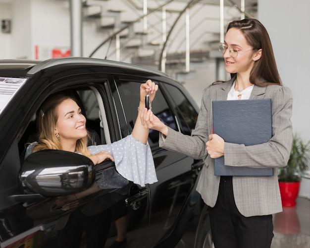 Blonde frau, die schlüssel von einem autohändler nimmt
