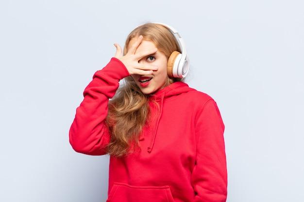 Blonde frau, die schockiert, ängstlich oder verängstigt aussieht, gesicht mit hand bedeckt und zwischen den fingern späht