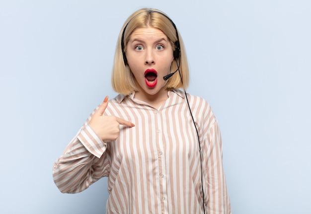 Blonde frau, die schockiert und überrascht mit offenem mund aussieht und auf sich selbst zeigt