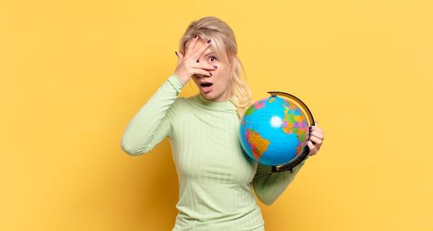 Blonde frau, die schockiert, verängstigt oder verängstigt aussieht, das gesicht mit der hand bedeckt und eine erdkugel hält