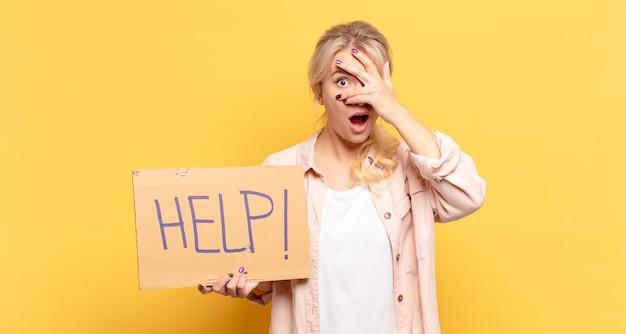 Blonde frau, die schockiert, verängstigt oder verängstigt aussieht, das gesicht mit der hand bedeckt und zwischen den fingern späht