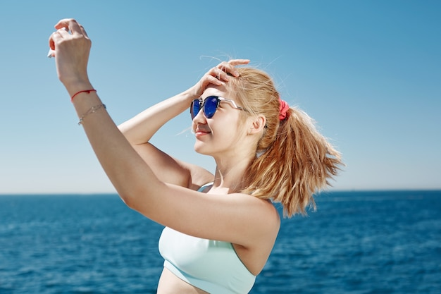 Blonde frau, die selfie am strand nimmt