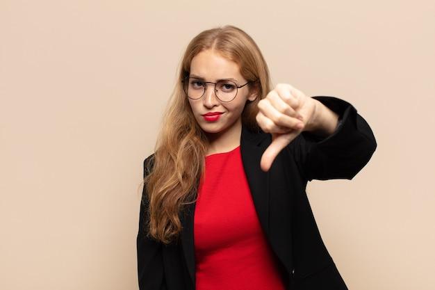 Blonde frau, die sich böse, wütend, verärgert, enttäuscht oder unzufrieden fühlt und mit einem ernsten blick die daumen nach unten zeigt