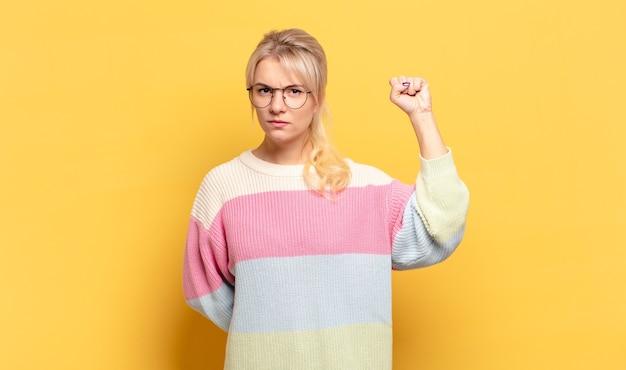 Blonde frau, die sich ernst, stark und rebellisch fühlt, die faust hebt, protestiert oder für die revolution kämpft